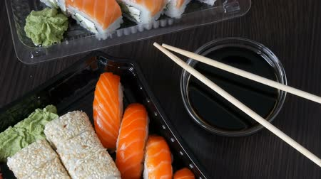 sake : Camera zooms. Large sushi set with a variety of sushi rolls as well as maki, nigiri, gunkan on a stylish black background. Close to soy sauce and wooden bamboo sticks. Top view