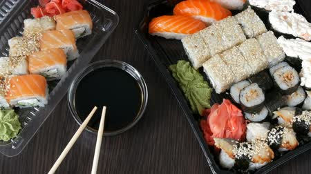 нигири : Big sushi set with variety of sushi rolls, maki, nigiri, gunkan on a stylish dark background. Soy sauce and bamboo chopsticks lie nearby