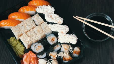 васаби : Large sushi sets with lots of sushi, roll, maki, nigiri, gunkan. Stylish sushi sets on black wooden table next to soy sauce and Chinese sticks