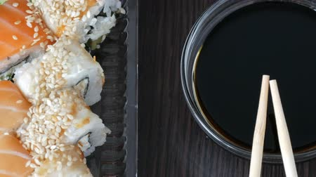 васаби : Stylishly laid sushi set on a black wooden background next to soy sauce and Chinese bamboo sticks. Various sushi rolls with salmon, eel, cucumber shrimps and other various stuffing