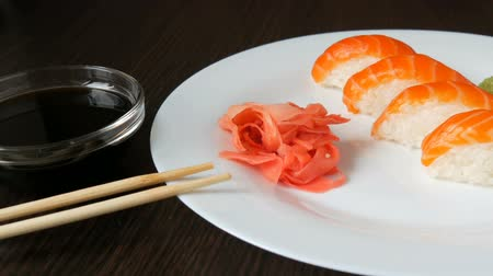 nori : Four large sushi with piece of salmon lie on a large flat plate. Camera zooms Stock Footage