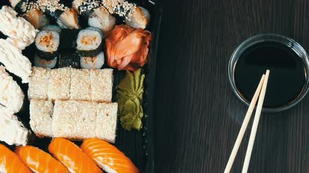 sake : Stylishly laid sushi set on a black wooden background next to soy sauce and Chinese bamboo sticks. Various sushi rolls with salmon, eel, cucumber shrimps and other various stuffing