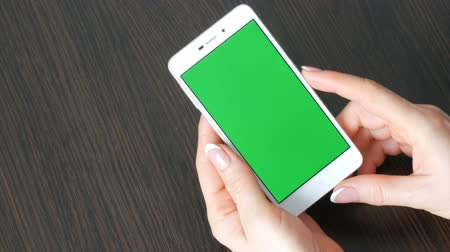 checkbook : Female hands with beautiful French manicure take a white smartphone with Green Screen. Using Smartphone,Holding Smartphone with Green Screen on a stylish black wooden table