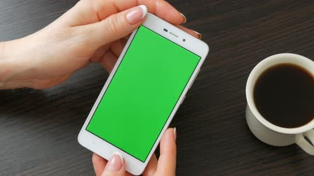 dragging : Female hands with beautiful French manicure take a white smartphone with Green Screen near white cup of coffee. Using Smartphone,Holding Smartphone with Green Screen on a stylish black wooden table Stock Footage