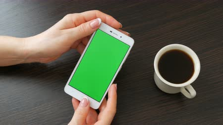 checkbook : Female hands with beautiful French manicure take a white smartphone with Green Screen near white cup of coffee. Using Smartphone,Holding Smartphone with Green Screen on a stylish black wooden table Stock Footage