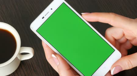 checkbook : Female hands with beautiful French manicure take a white smartphone with Green Screen near white cup of coffee. Using Smartphone,Holding Smartphone with Green Screen Stock Footage
