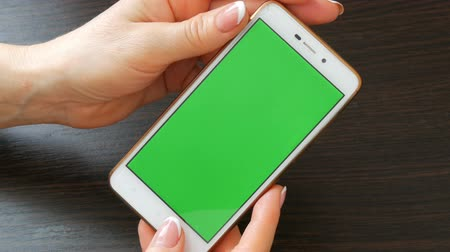 checkbook : Female hands with beautiful French manicure take a white smartphone with Green Screen. Using Smartphone,Holding Smartphone with Green Screen