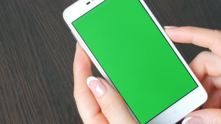 dedo indicador : Female hands with beautiful French manicure take a white smartphone with Green Screen. Using Smartphone,Holding Smartphone with Green Screen on a stylish black wooden table