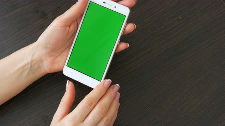 dragging : Female hands with beautiful French manicure take a white smartphone with Green Screen. Using Smartphone,Holding Smartphone with Green Screen