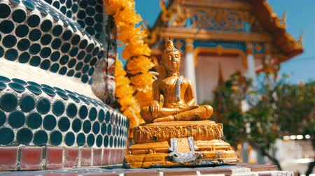 pozlacený : Golden Buddhist Buddha statue on the background of a beautiful gilded temple with a variety of ornaments and religious symbols