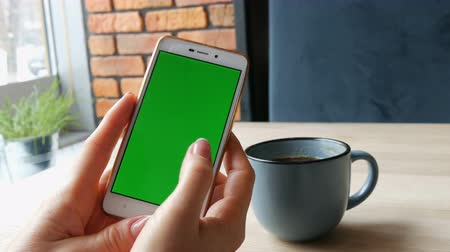 dragging : Green screen smartphone. Chroma Key on a white smartphone, female hands hold mobile phone in a cafe next to a cup of coffee
