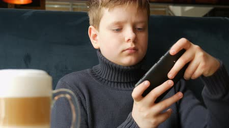 boyish : Boy teen playing a game on black smartphone Stock Footage