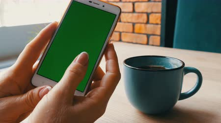 cardíaco : Green screen smartphone. Chroma Key on a white smartphone, female hands hold mobile phone in a cafe next to a cup of coffee