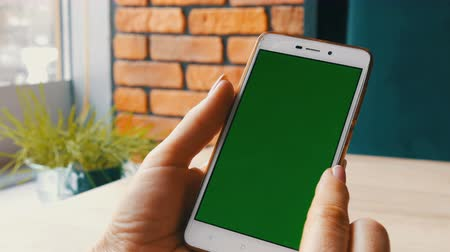 dedo indicador : Green screen smartphone. Chroma Key on a white smartphone, female hands hold mobile phone in a cafe