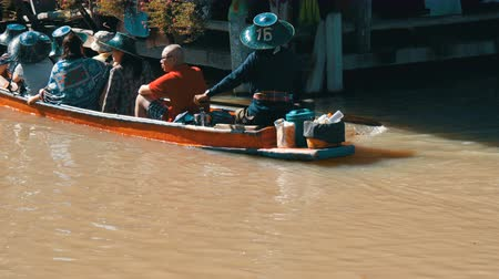 fly fishing : People are swimming in a boat on a brown river in Thailand in the haze. Walking people along the shore and riding on river in a boat. Pattaya Floating Market