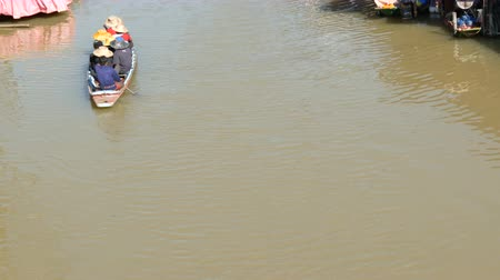 fly fishing : People are swimming in a boat on a brown river to Thailand. A garland of white lamps on a background walking people along the shore and riding on river in a boat. Pattaya Floating Market