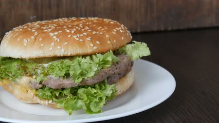 majonez : Large triple burger with lettuce leaves on a white plate. Hamburger on a stylish wooden background. Fast food