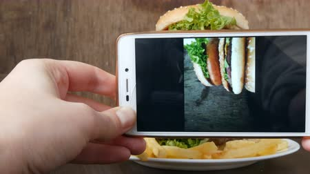 bacon burger : Female hand makes photo on the smartphone of a beautiful juicy hamburger with lettuce leaves on a stylish wooden background Stock Footage