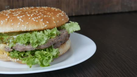 mayonez : A large delicious juicy burger with triple cutlet, fresh lettuce leaf and cheese lies on a white plate on a stylish wooden background Stok Video