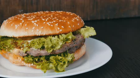 white onion : Large triple burger with lettuce leaves on a white plate. Hamburger on a stylish wooden background. Fast food