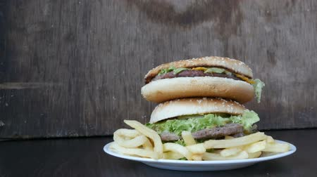mustár : A womans hand takes a burger from a large mountain of three delicious juicy burgers with lettuce leaves and cheese. Hamburgers lie one on top of another on a stylish wooden background. Fast food Stock mozgókép