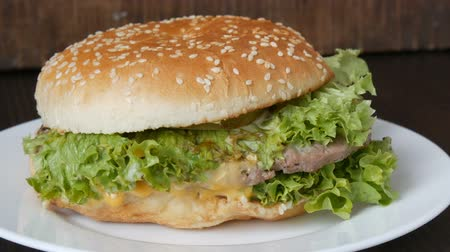 mustár : Large triple burger with lettuce leaves on a white plate. Hamburger on a stylish wooden background. Fast food