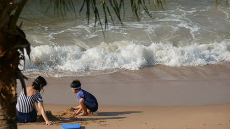 pursue : PATTAYA, THAILAND - DECEMBER 25, 2017: Little boy in a swimming suit makes something of sand with his mother. Beach with tall palm trees Stock Footage