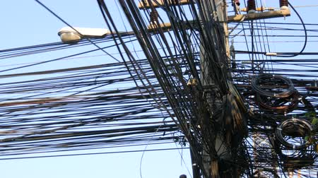 změť : Tangled bundles of overhead wires. Electricity system on streets of Pattaya, Thailand. Tangle of wires on overloaded utilities pole in Thailand wire level pan