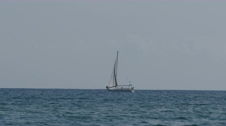 hajózik : Beautiful white sailboat on the horizon, floating on a sea