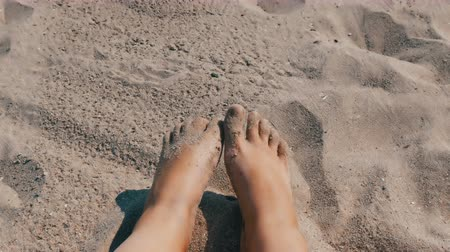 suntan : Female tanned legs and fingers move against background of sand on the beach