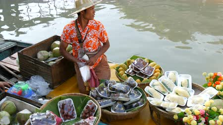 buying food : PATTAYA, THAILAND - December 18, 2017: Seller in a colorful shirt and a straw hat sells exotic Thai fruits on a boat
