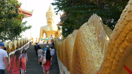 клык : PATTAYA, THAILAND - December 18, 2017: Tourists visiting BIg Buddha Hill, an attractive place .A huge image of Buddha at the top of hill. Majestic stairs with statues of dragons
