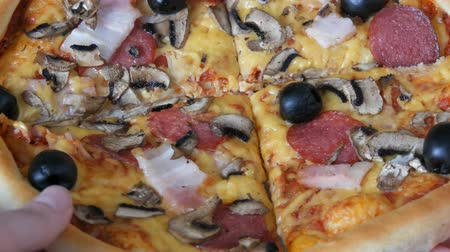top chef : Hand take a piece of a Big Italian pizza with black olives, bacon, salami and cheese close up
