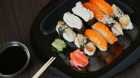 васаби : Stylish black sushi set on flat plate with different kinds of roll, nigiri, maki, gunkan. Japanese national cuisine