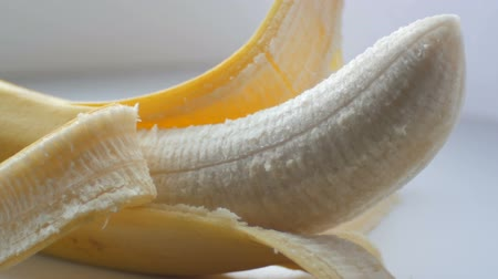 pecker : Body banana with the peel on a white background macro close up view Stock Footage