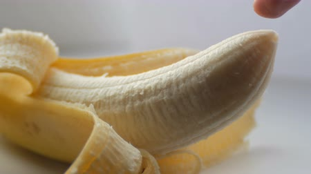 intimita : Woman sexually touching with a finger tip of purified banana, macro close up view