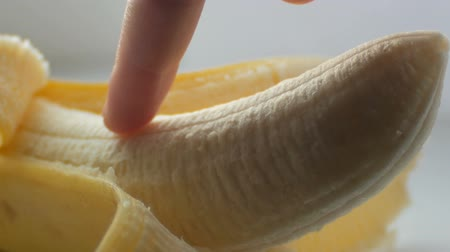 meghittség : Woman sexually touching with a finger of purified banana, macro close up view