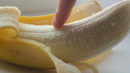 pecker : Woman sexually touching with a finger of purified banana, macro close up view
