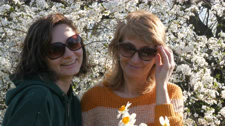 żonkile : Portrait of adult middle-aged mother and her adult daughter who Look around and smile happily on Mothers Day against the background of a flowering tree Wideo