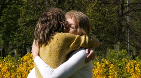 anne : An adult daughter runs up and meets an elderly adult mother hugging her and kissing her. Spring Mothers Day