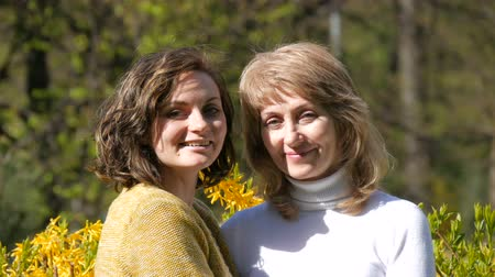 atender : Adult beautiful daughter and elderly adult beautiful mother looking into camera and smiling in the spring afternoon Stock Footage
