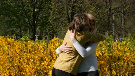 den matek : An adult daughter runs up and meets an elderly adult mother hugging her and kissing her. Spring Mothers Day
