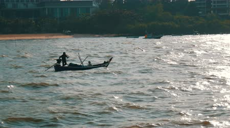 fly fishing : Two Thai fishermen sail on small wooden boat on strong waves to fish Stock Footage
