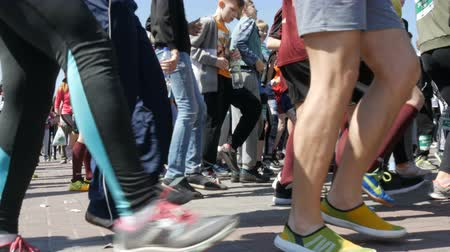 squats : April 21, 2018 - Kamenskoye, Ukraine: large number of peoples legs make a warm-up before the marathon race. Jumps and squats of a large number of people in the square