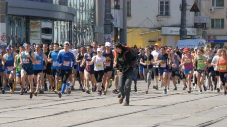 squats : April 21, 2018 - Kamenskoye, Ukraine: Marathon race, people run from the start, the cameraman with camera runs ahead of the crowd