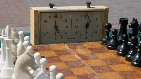 storming : April 21, 2018 - Kamenskoye, Ukraine: Black and white chess stand on the board, next to a vintage chess clock on street