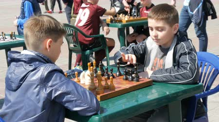 initial : April 21, 2018 - Kamenskoye, Ukraine: Children play chess in street. Street Chess Tournament outdoor