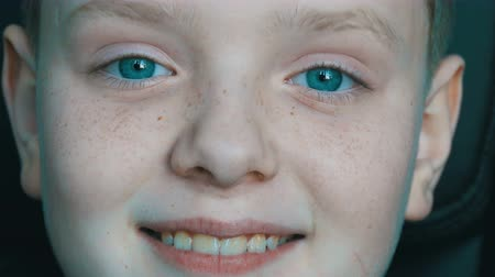 looking distance : Cheerful blond boy with a teenager with freckles on his face and unusual turquoise eyes looking at camera and fooling happy Stock Footage