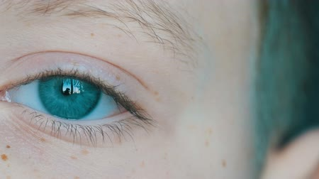 sentido : Turquoise eyes of blond boy teenager with red freckles on his face and long white eyelashes close up view