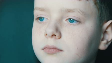 schoolkid : Face of beautiful teenager with freckles close-up view. A boy with unusual turquoise eyes looking into the distance Stock Footage